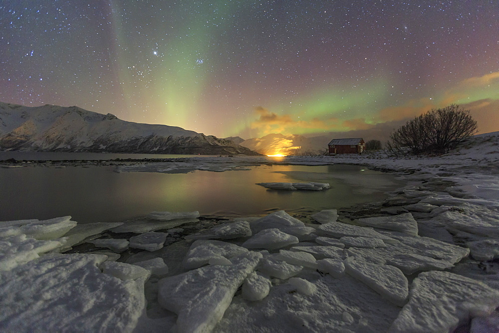 The Northern Lights illuminates the icy landscape in Svensby, Lyngen Alps, Troms, Lapland, Norway, Scandinavia, Europe