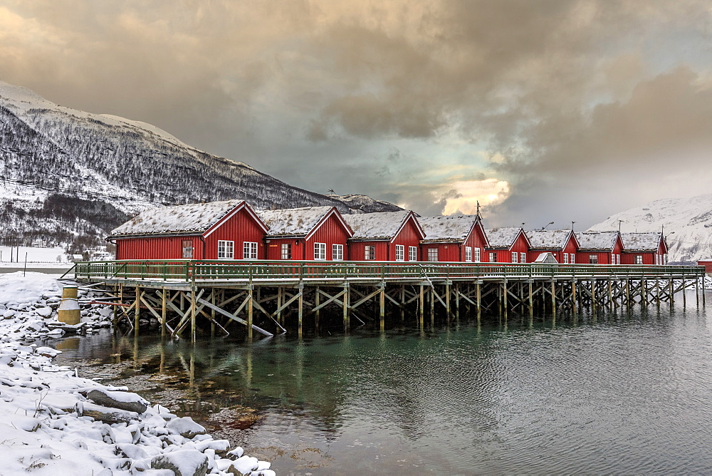 Typical red wooden huts of fishermen in the snowy and icy landscape of Lyngen Alps, Troms, Lapland, Norway, Scandinavia, Europe