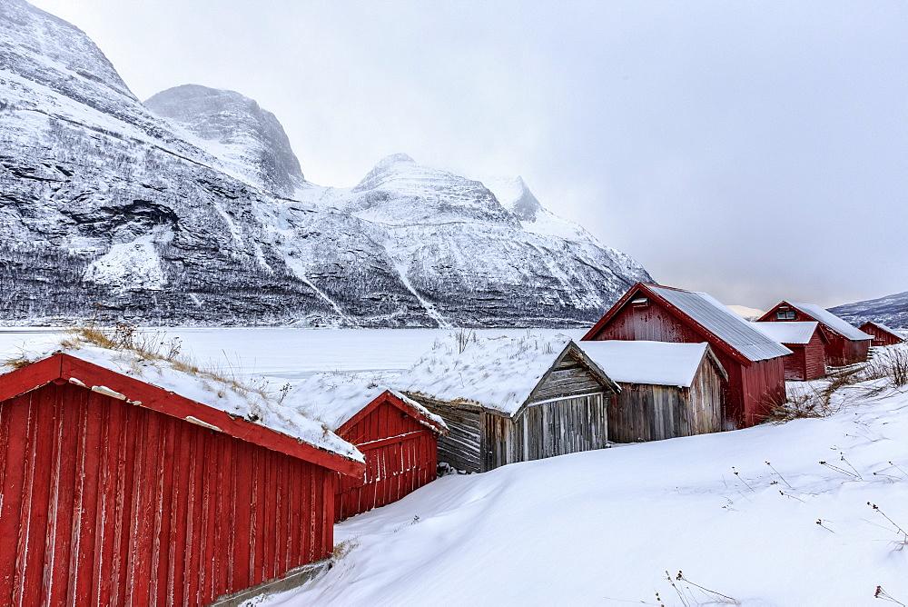 Typical wooden huts in the snowy landscape of Lyngseidet, Lyngen Alps, Tromso? Lapland, Norway, Scandinavia, Europe