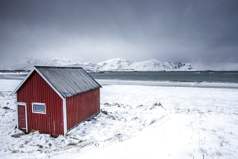 A typical house of the fishermen called rorbu on the snowy beach frames the icy sea at Ramberg, Lofoten Islands, Arctic, Norway, Scandinavia, Europe