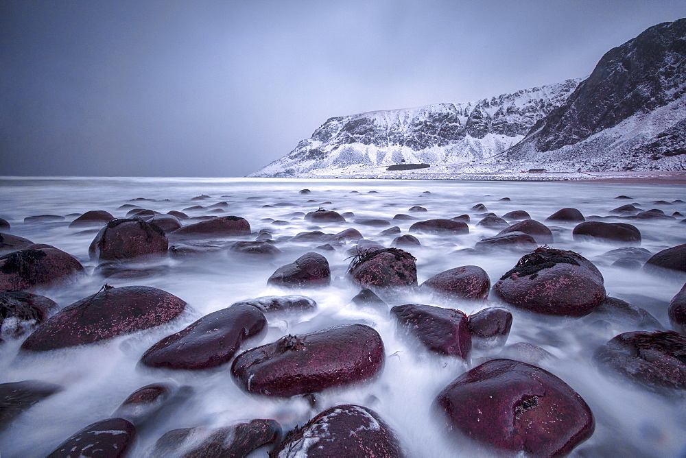 Rocks on the beach modeled by the wind surround the icy sea, Unstad, Lofoten Islands, Arctic, Norway, Scandinavia, Europe