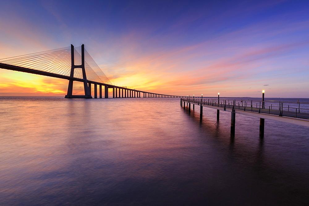 The colors of dawn on Vasco da Gama Bridge that spans the Tagus River, Lisbon, Portugal, Europe