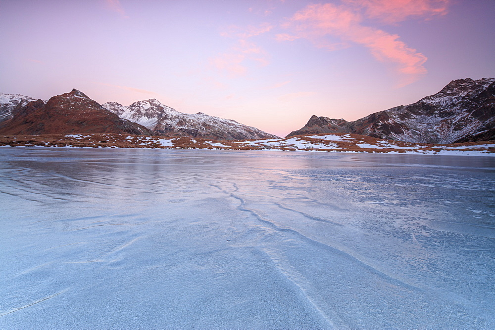 Pink lights of dawn on the snowy peaks around the frozen surface of Andossi Lake, Spluga Valley, Valtellina, Lombardy, Italy, Europe