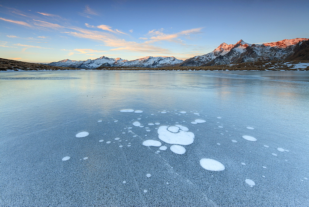 Ice bubbles on the frozen surface of Andossi Lake at sunrise, Spluga Valley, Valtellina, Lombardy, Italy, Europe