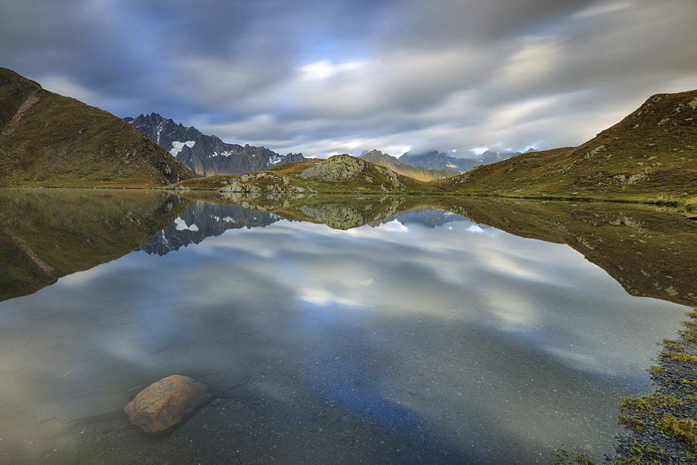 The snowy peaks are reflected in Fenetre Lakes at dawn, Ferret Valley, Saint Rhemy, Grand St Bernard, Aosta Valley, Italy, Europe