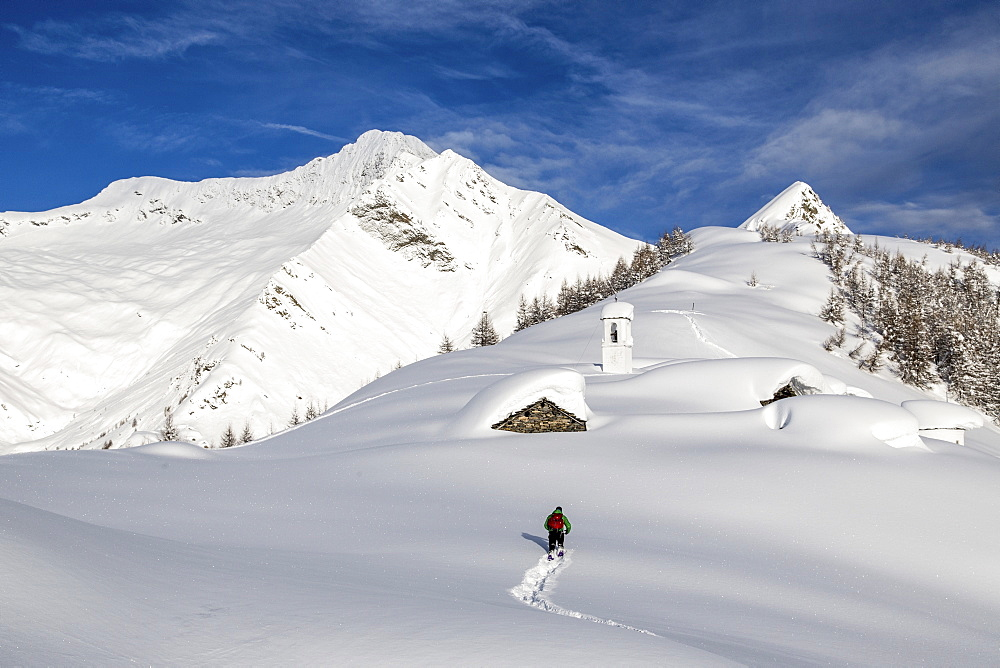 A hiker trying to approach the little village at the Scima Alp covered in snow, Valchiavenna, Lombardy, Italy, Europe