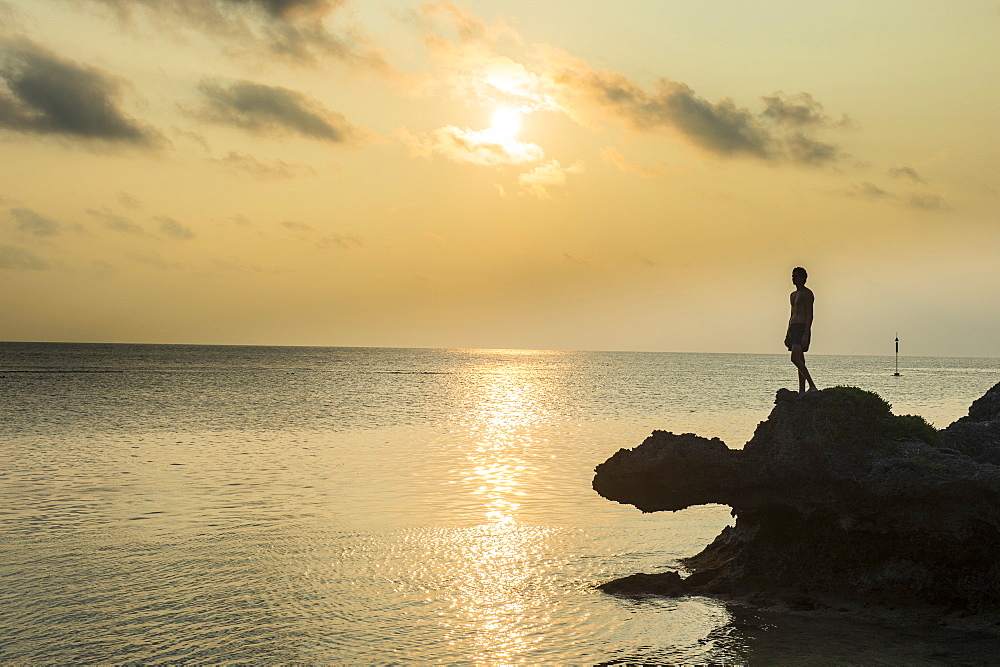 Man on a rock in backlight on the rocky west coast in Ouvea, Loyalty Islands, New Caledonia, Pacific