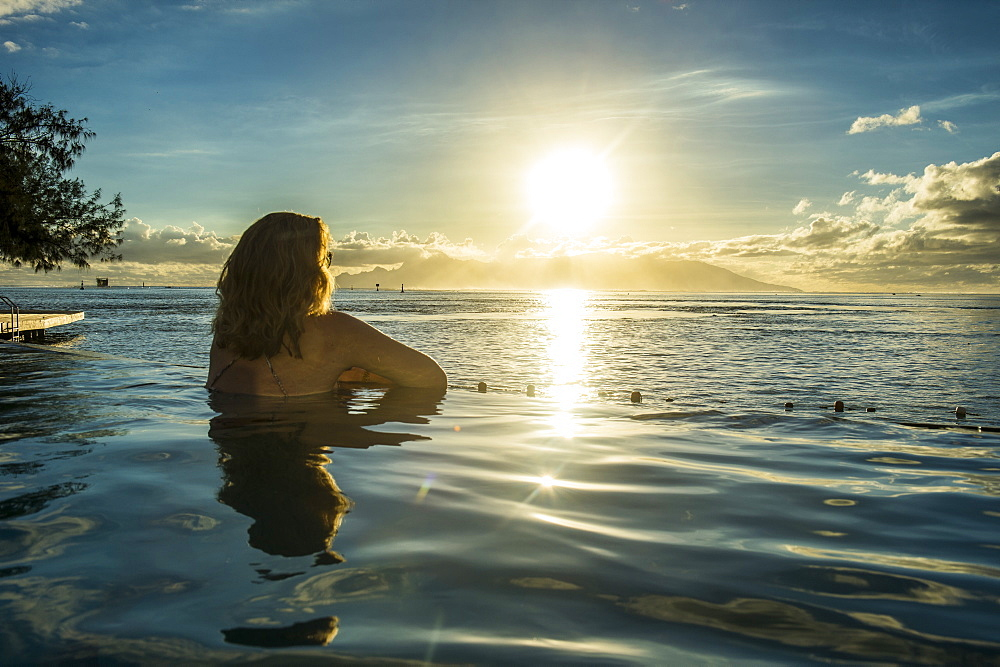 Woman enjoying the sunset in a swimming pool with Moorea in the background, Papeete, Tahiti, Society Islands, French Polynesia, Pacific