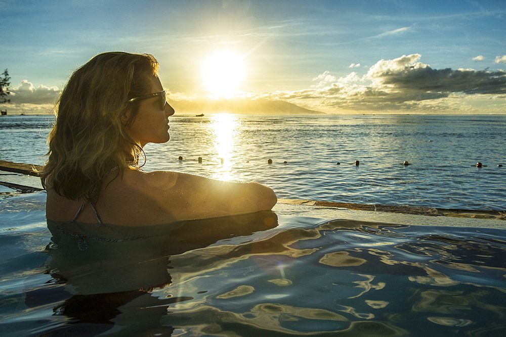 Woman enjoying the sunset in a swimming pool with Moorea in the background, Papeete, Tahiti, French Polynesia