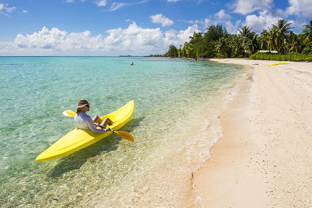 Woman kayaking in the turquoise waters of Tikehau, Tuamotus, French Polynesia, Pacific