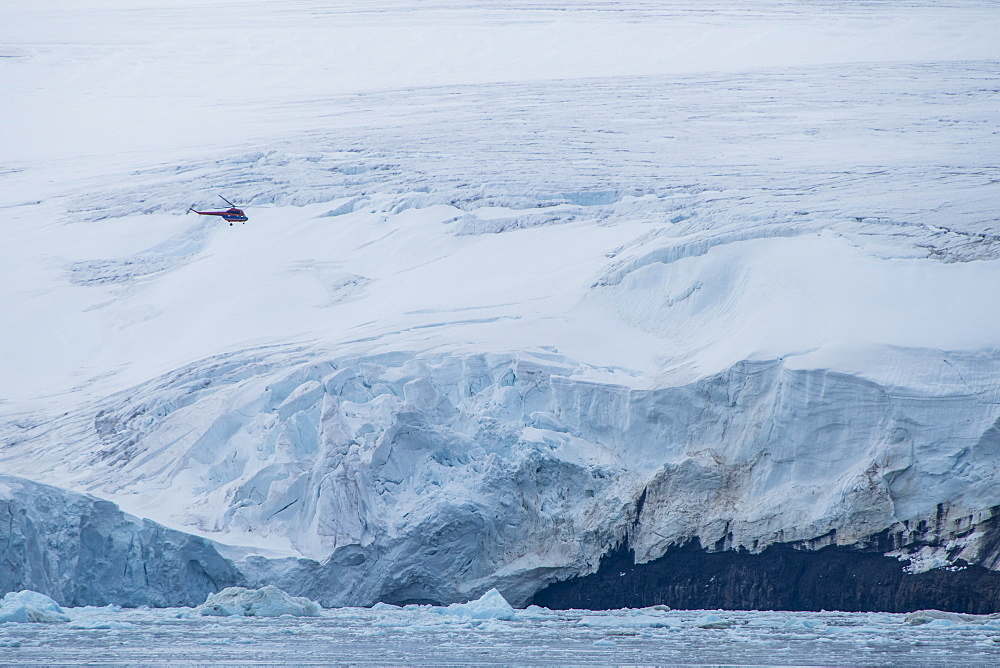 Helicopter flying over the giant icefield of Alexandra Land, Franz Josef Land archipelago, Russia