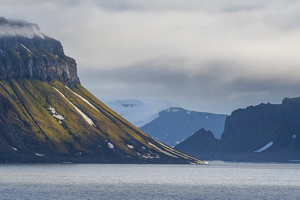Green cliff in the glacier covered moutains of Franz Josef Land archipelago, Russia