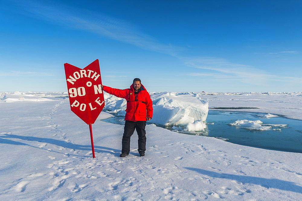 Man posing with a sign on the North Pole, Arctic