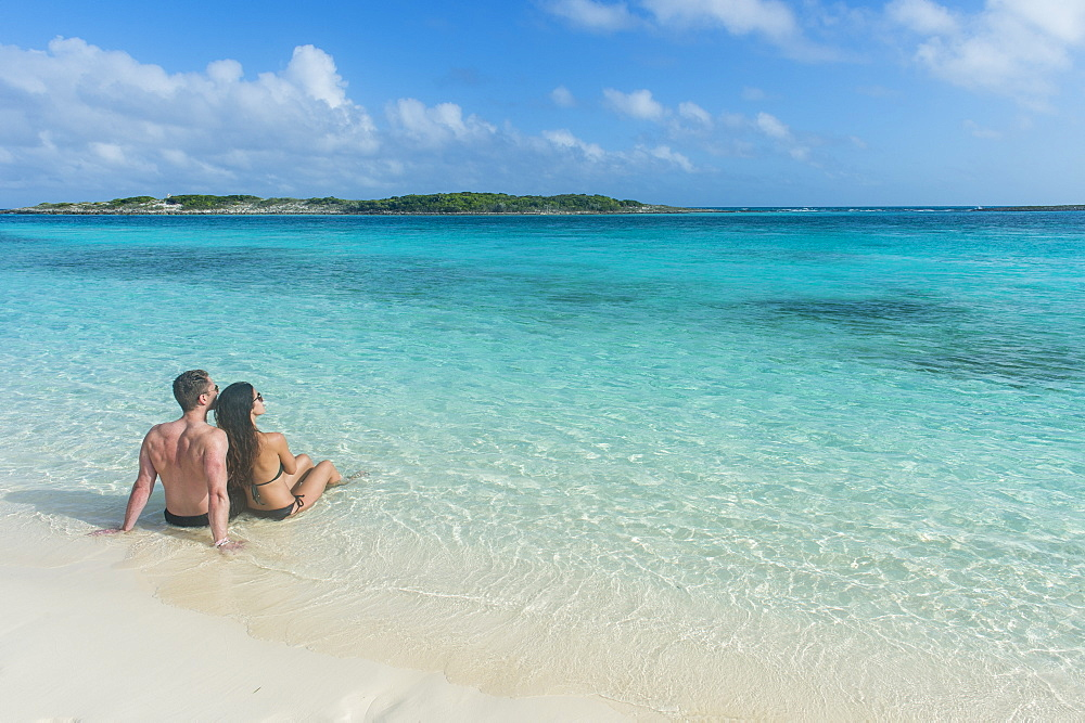 Couple sitting on a white sand beach in the turquoise waters of the Exumas, Bahamas, West Indies, Caribbean, Central America