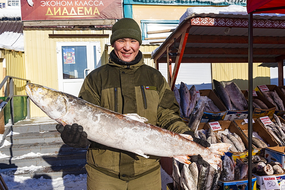 Local fishseller holding a huge frozen fish, Fish and meat market, Yakutsk, Sakha Republic (Yakutia), Russia, Eurasia