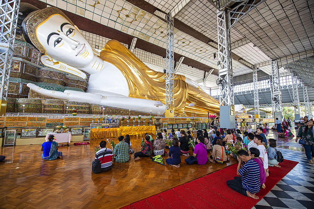 Pilgrims praying before the reclining Buddha, Shwethalyaung Temple, Bago, Myanmar (Burma), Asia