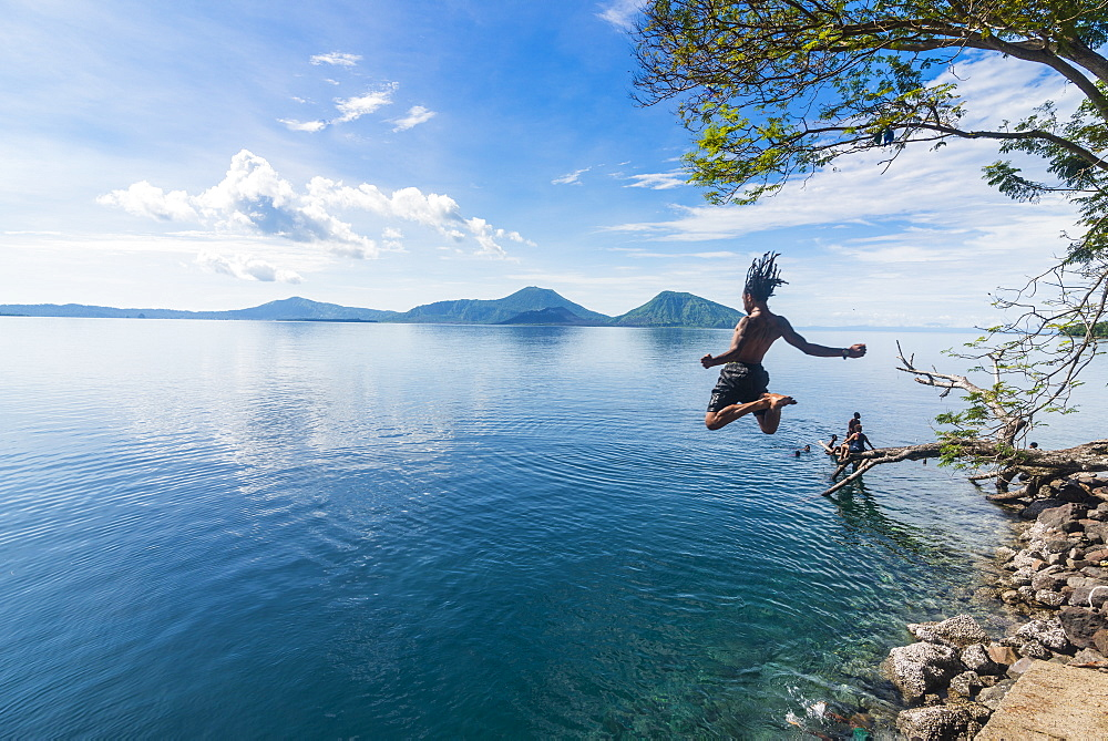 Man jumping in the bay of Rabaul with Volcano Tavurvur in the background, East New Britain, Papua New Guinea, Pacific