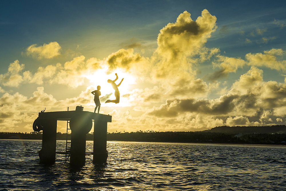 Backlit local boys jumping into the water of the lagoon of Wallis from a platform, Wallis and Futuna, Pacific