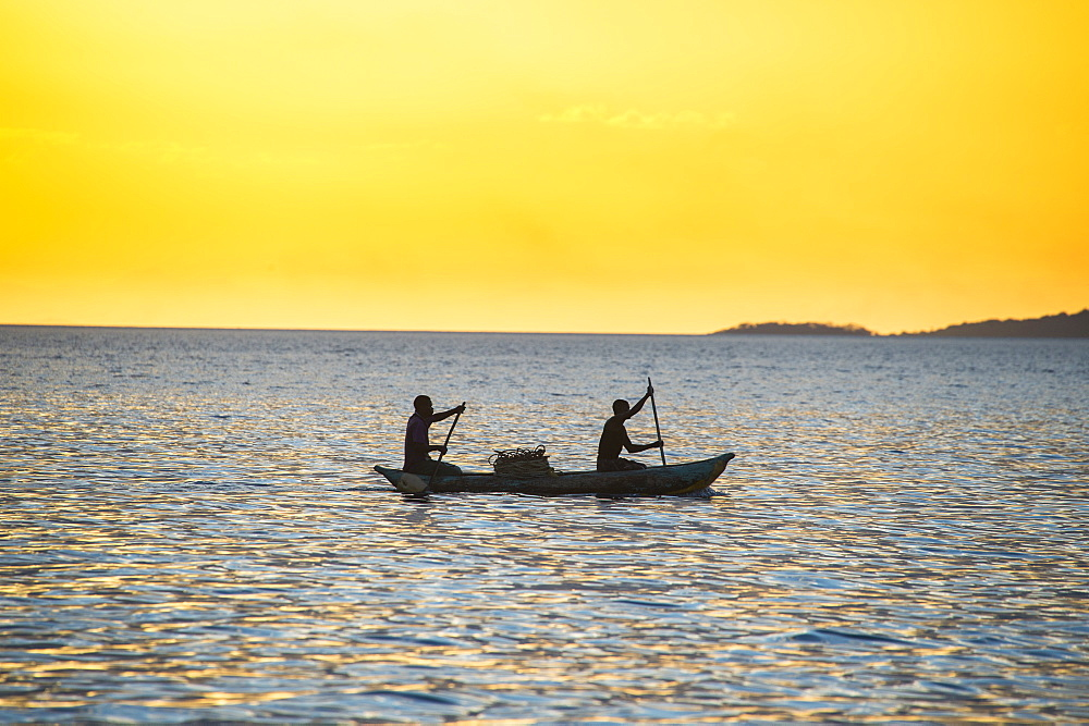 Backlight of fishermen in a little fishing boat at sunset, Lake Malawi, Cape Maclear, Malawi, Africa