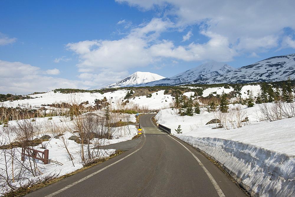 Road leading through the snow capped mountains of the Daisetsuzan National Park, UNESCO World Heritage Site, Hokkaido, Japan, Asia