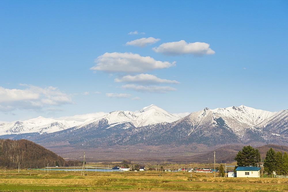Farmland below the mountains of the Daisetsuzan National Park, UNESCO World Heritage Site, Furano, Hokkaido, Japan, Asia