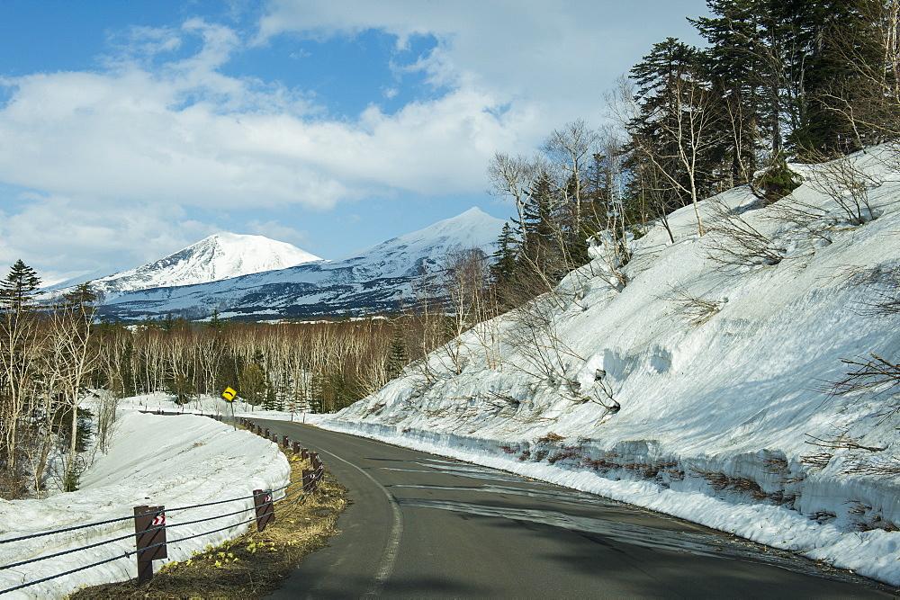 Road leading through the snow capped mountains of the Unesco world heritage sight Daisetsuzan National Park, Hokkaido, Japan