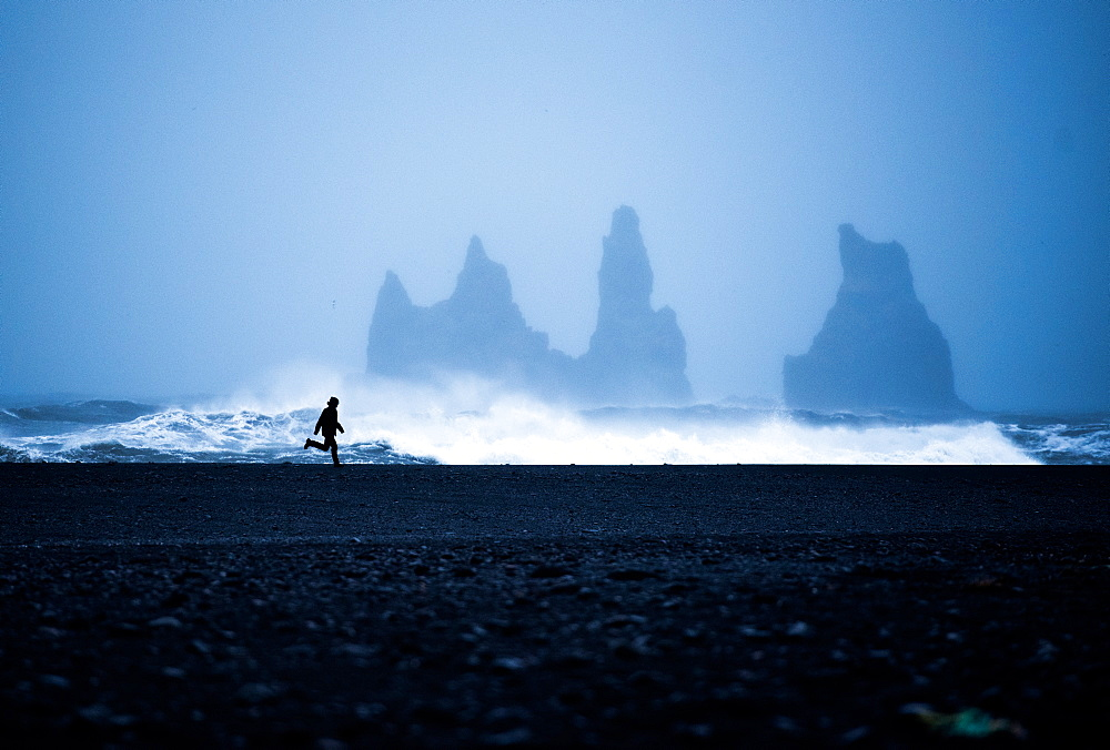 Tourist running on Black Sand Beach, Iceland