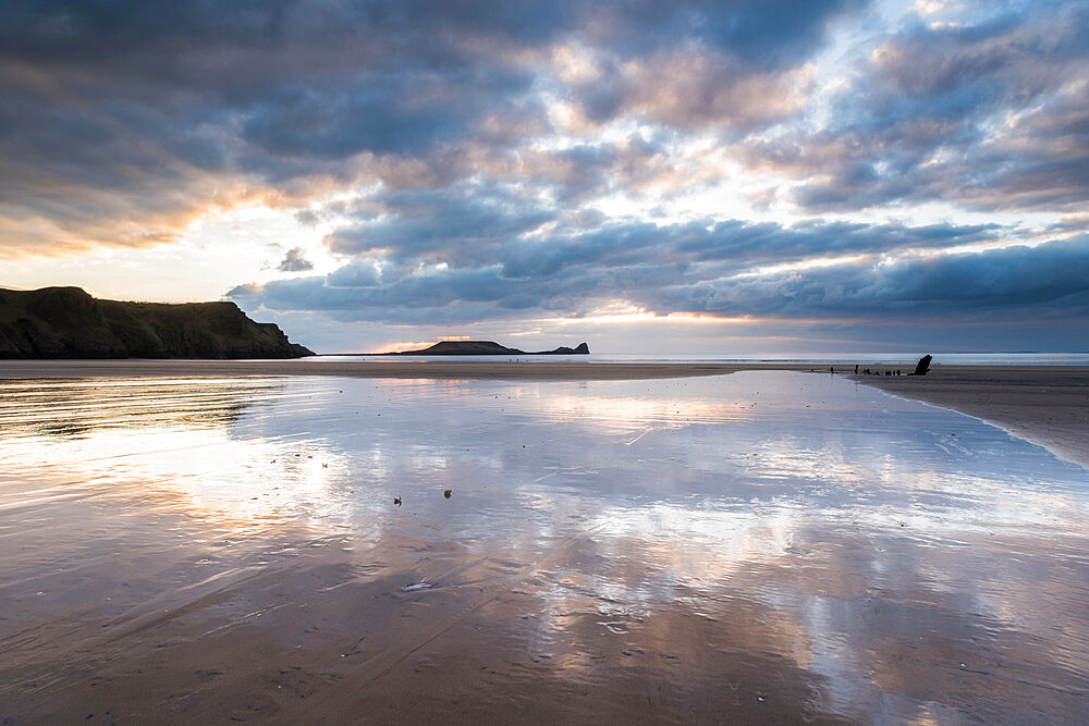 Sunset clouds reflected in wet sand, Rhossili Bay, Gower Peninsula, South Wales, United Kingdom, Europe