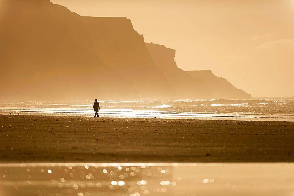 Person walking along beach in the evening sunlight, Rhossili, Gower Peninsula, Swansea, Wales. - 1200-382