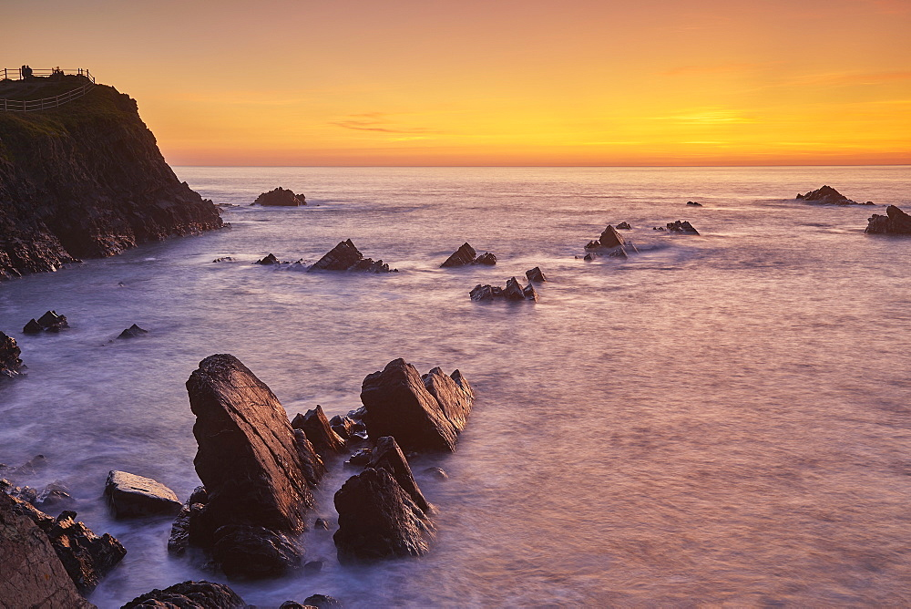 The cliffs and rocks of Devon's Atlantic coast, at Hartland Quay, seen during a calm evening sunset.