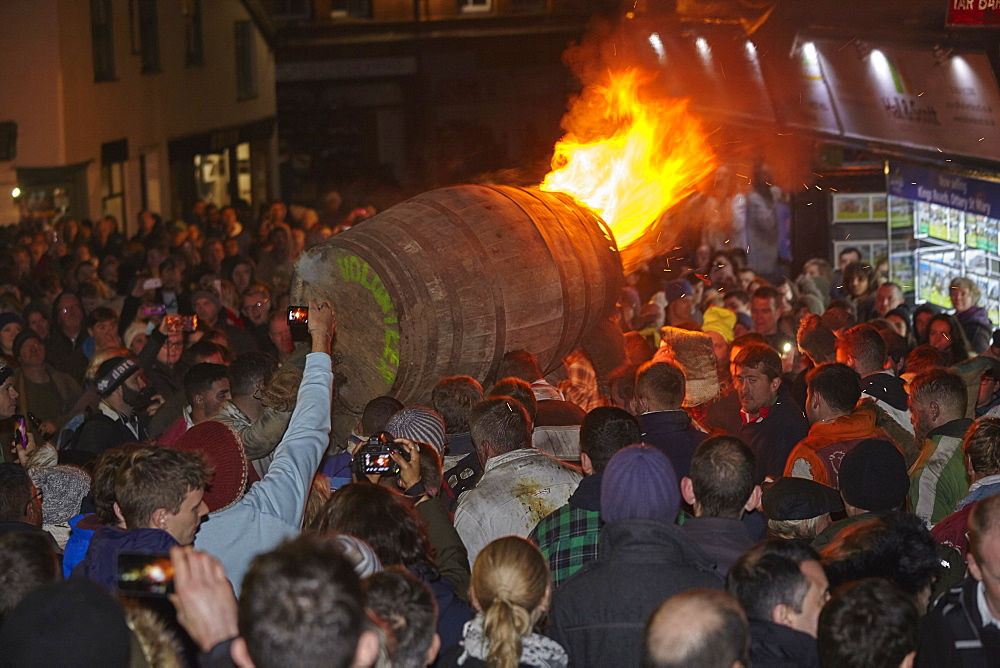 A blazing tar barrel passes through crowded streets during the annual Ottery Tar Barrel Festival, held in early November, Ottery St. Mary, Devon, England, United Kingdom, Europe