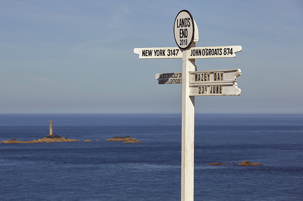 A signpost at Land's End, Britain's most southwesterly point, with Longships Lighthouse and the Atlantic Ocean behind; Cornwall.