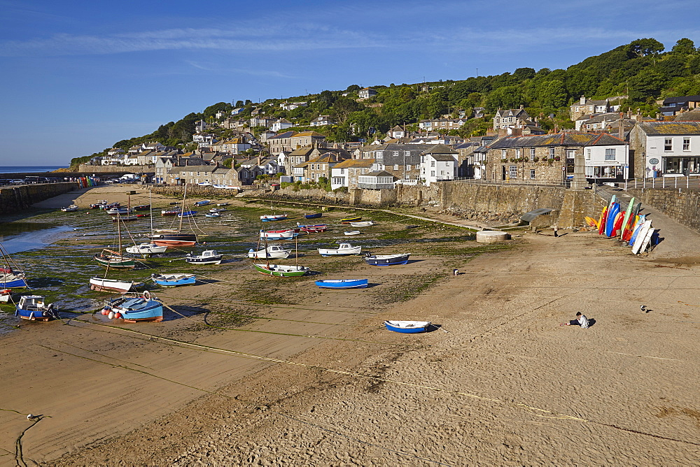 The harbour at Mousehole, an historic and archetypal Cornish fishing village, seen at low tide; near Penzance, west Cornwall.