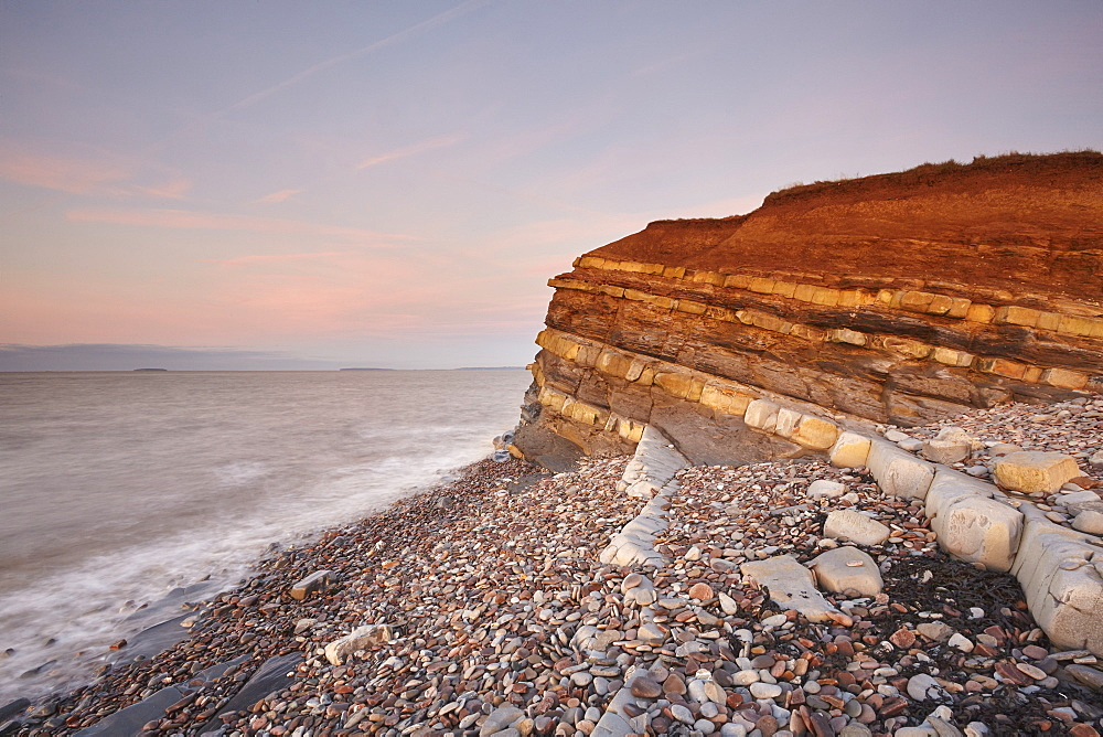 Evening light on rocks and the cliff at Kilve beach, Kilve, near Nether Stowey, Somerset, Great Britain.