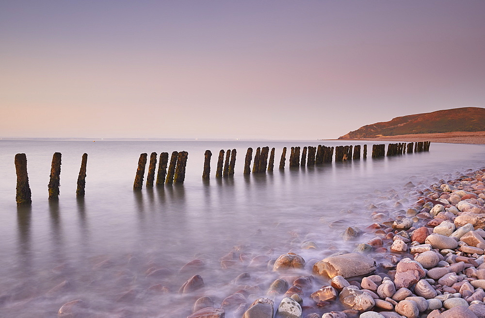A dusk view of rotting sea defences on the pebble beach at Porlock Weir, near Porlock, in Exmoor National Park, Somerset.