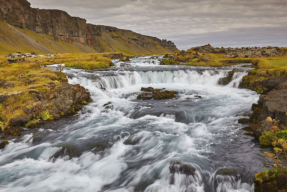 A classic Icelandic landscape, a river flowing along the base of a cliff, The Fossalar River, near Kirkjubaejarklaustur, Iceland, Polar Regions - 1202-432