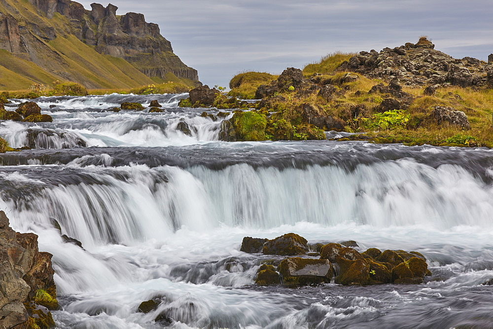 A classic Icelandic landscape, a river flowing along the base of a cliff, The Fossalar River, near Kirkjubaejarklaustur, Iceland, Polar Regions - 1202-433