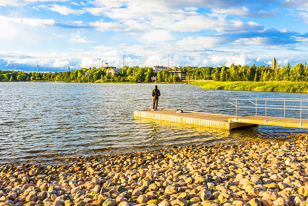 A man fishing on a jetty at Toolo Bay (Toolonlahti), Helsinki, Uusimaa, Finland, Scandinavia, Europe
