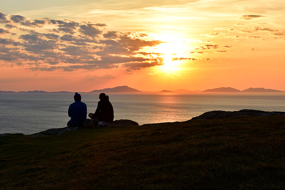 Two tourists enjoying a beautiful sunset at Neist Point on the Isle of Skye, Outer Hebrides, Scotland, UK