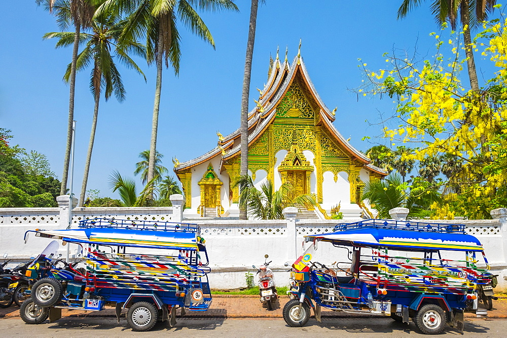 Colorful tuk-tuks in front of Haw Pha Bang temple on the grounds of the Royal Palace Museum in Luang Prabang, Louangphabang Province, Laos, Indochina, Southeast Asia, Asia