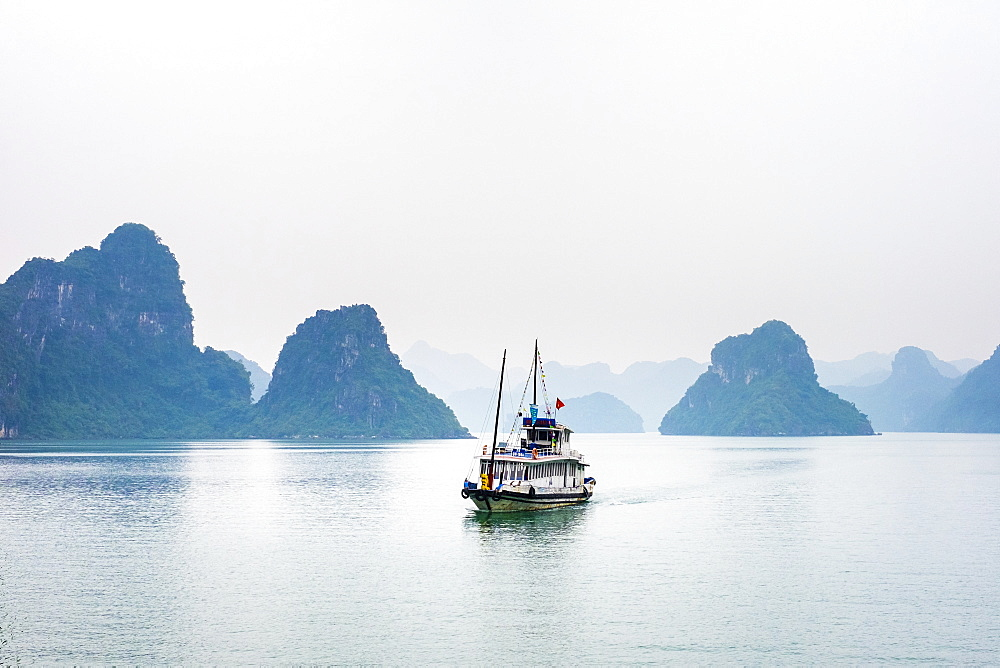 A boat passes through foggy karst landscape in Ha Long Bay, Quang Ninh Province, Vietnam, Indochina, Southeast Asia, Asia