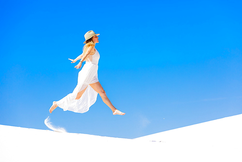 Woman jumping on the Gypsum Sand Dune, White Sands, New Mexico, United States of America, North America