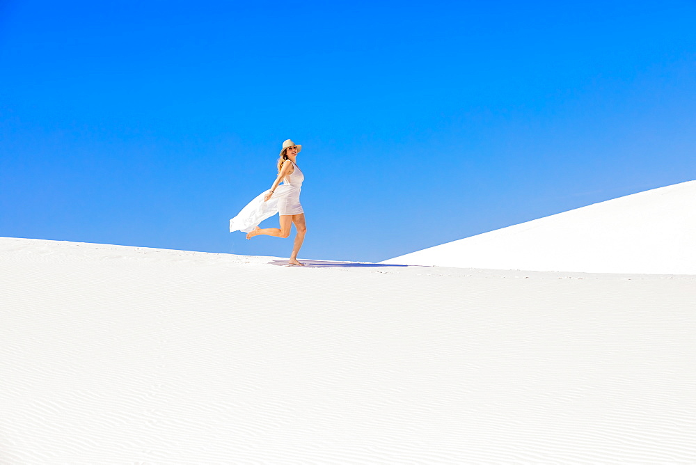Woman walking across Gypsum Sand Dune, White Sands, New Mexico, United States of America, North America