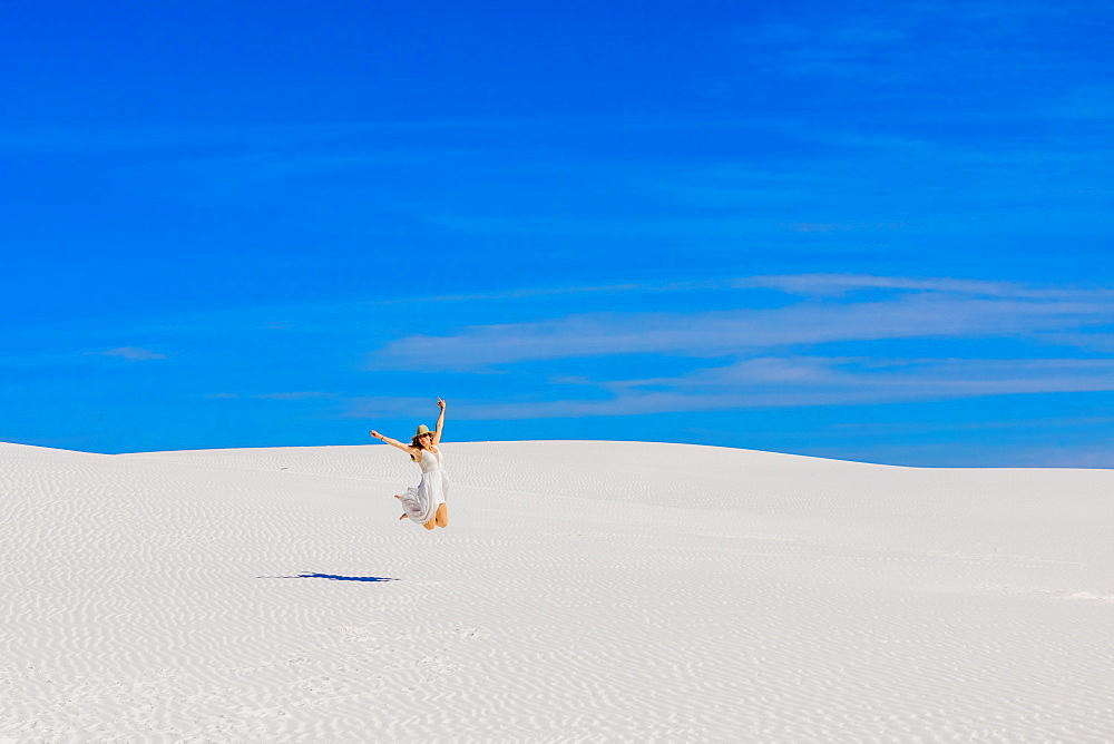 Woman jumping on Gypsum Sand Dune.