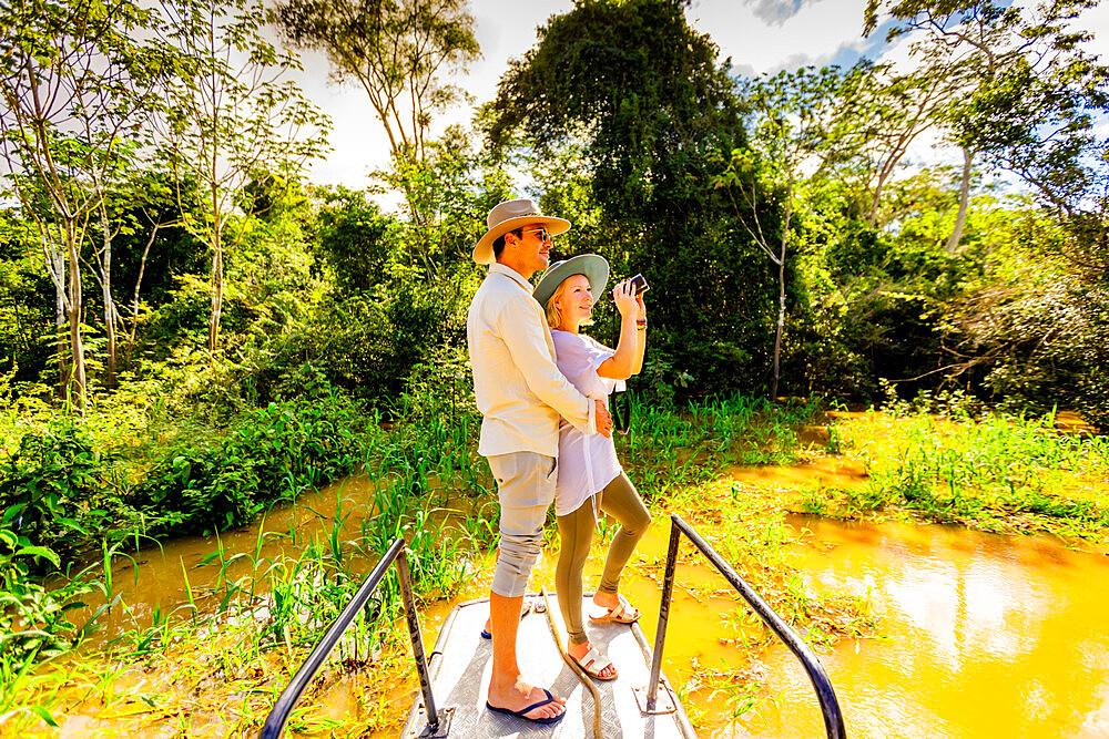 Couple searching for wildlife on a boat tour of the Amazon River.