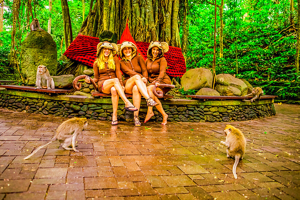 Women posing with the monkeys for a picture at the Sacred Monkey Forest Ubud. Home to 700 monkeys.