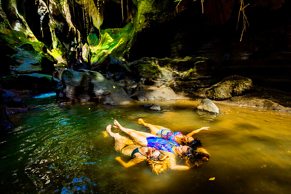 Women floating peacefully in the water at the Beji Guwang Hidden Canyon, Bali, Indonesia, Southeast Asia, Asia