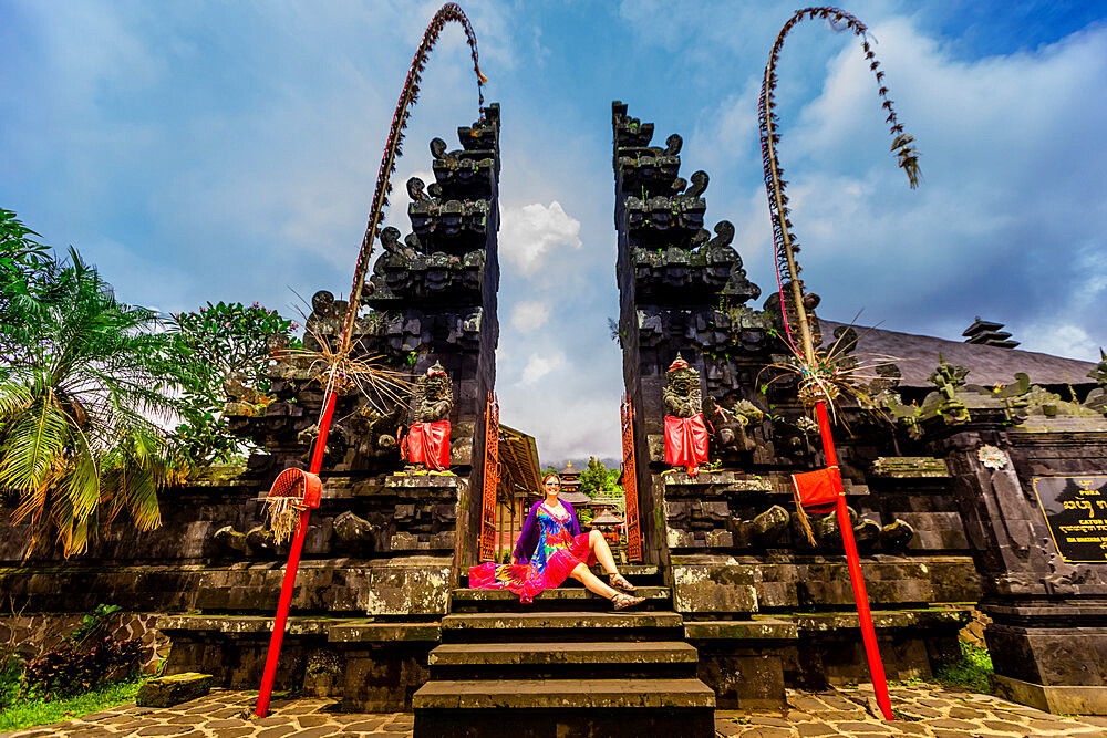 Woman posing for photo at the Besakih Temple, the most important, largest, and holiest temple of Hindu religion in Bali.