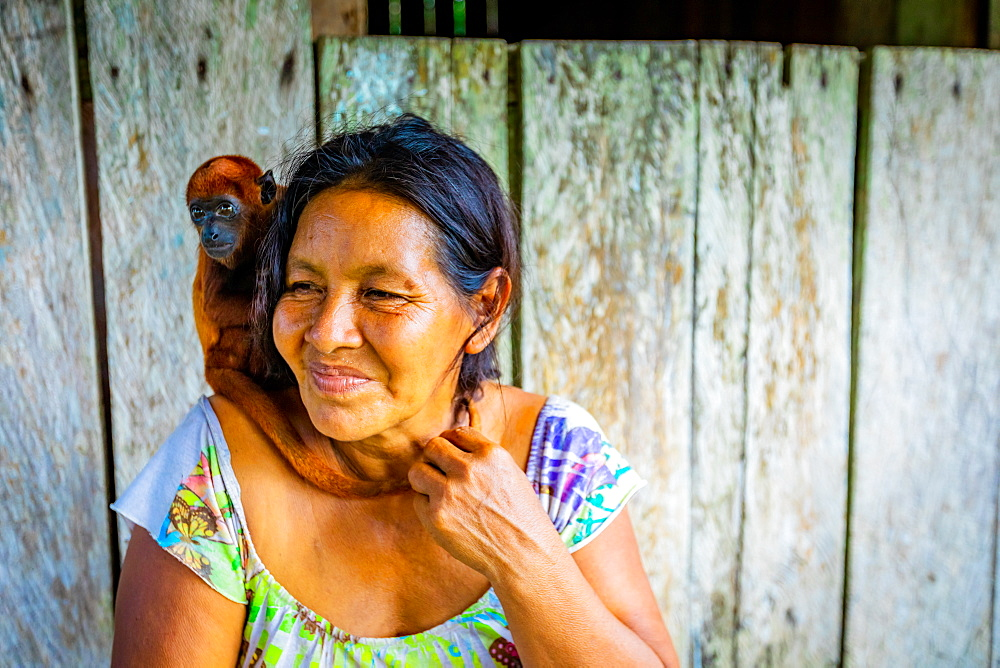 Woman and her rescued monkey at a local village on the Amazon River, Peru, South America