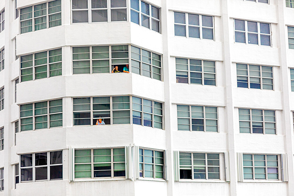 People without balconies cope with the pandemic lockdown through their windows at the Four Ambassadors Apartment Building, Miami, Florida, United States of America, North America - 1218-1280